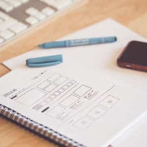 web designer sketching a wireframe layout ideas in a notebook picjumbo com 1 300x300